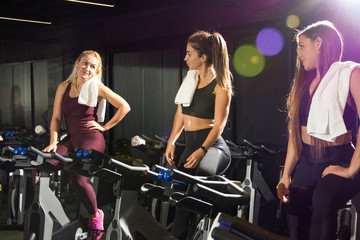 Athletic girls communicating on a break after cycling training in the gym.