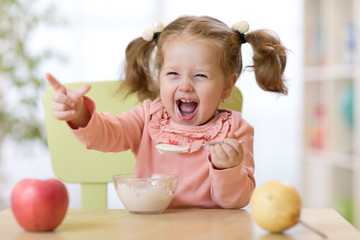 Funny child eating healthy food with a spoon at home