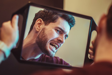 Young man checking their teeth at mirror after dental treatment - People bodycare and stomatology concept for healthy lifestyle - Focus on man face -