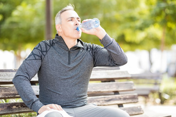 Mature man drinking water to refresh after a workout
