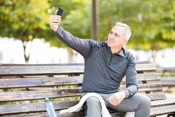 Mature man taking a selfie after exercising in park