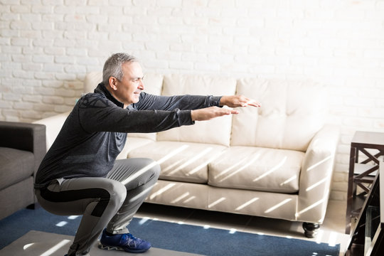Mature man doing squats workout at home