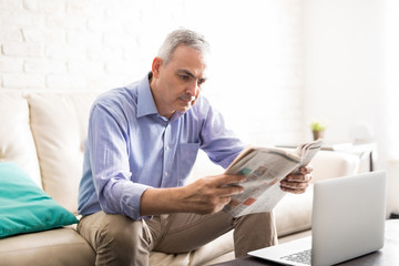 Good looking man reading a newspaper at home