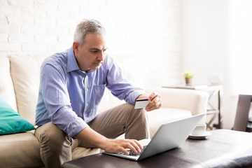 Mature man doing some online purchase with credit card