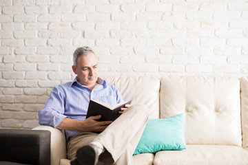 Hispanic man reading a novel at home