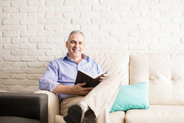 Handsome mature man reading a book to pass time