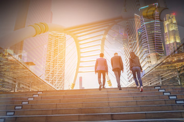 Double exposure image of Rear view of business team climbing stairs go to a city. Business concept