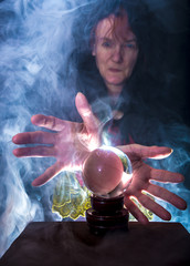 A fortune teller works in a dark room with a crystal ball