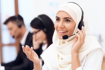 An Arab woman works in a call center. Arabian works at office.