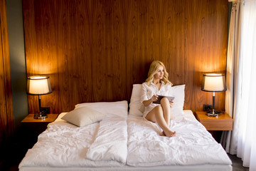 Blonde young woman using digital tablet in bed