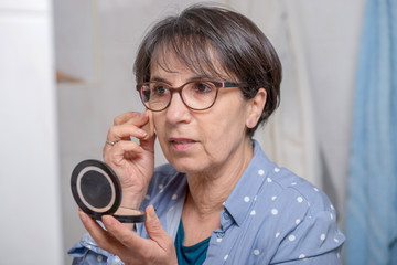 mature woman doing makeup while looking at small mirror