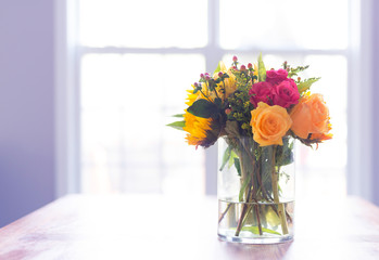 Bought of fresh flowers on a kitchen table backlit by windows