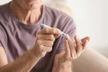 Elderly man with diabetes measuring level of blood sugar at home, closeup