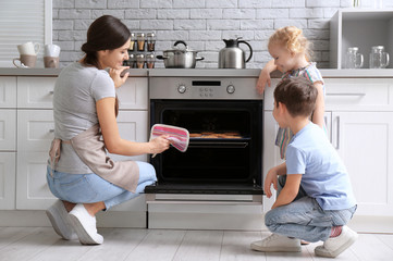 Little kids watching their mother bake cookies in oven indoors