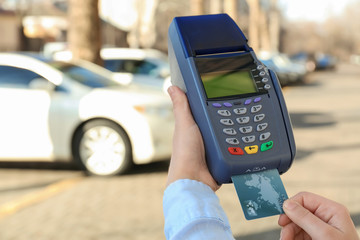 Woman using bank terminal for credit card payment outdoors