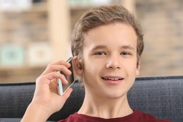 Teenage boy with hearing aid talking on phone indoors