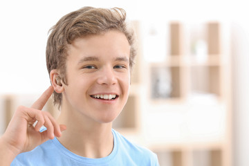 Teenage boy with hearing aid indoors