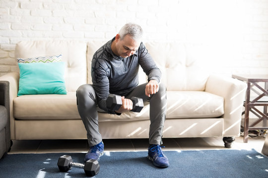 Middle aged man exercising with dumbbells at home