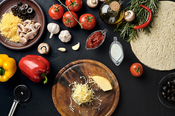 Cheese, different vegetables on black table. Ingredients for traditional italian pizza.