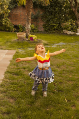 Child dress up dancing lookin up. Outdoor. Freedom. High angle.