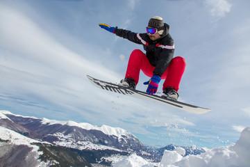 Uomo che salta con lo snowboard