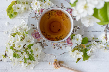 cup of tea in fine china surrounded by white spring flower blossoms on white table top view