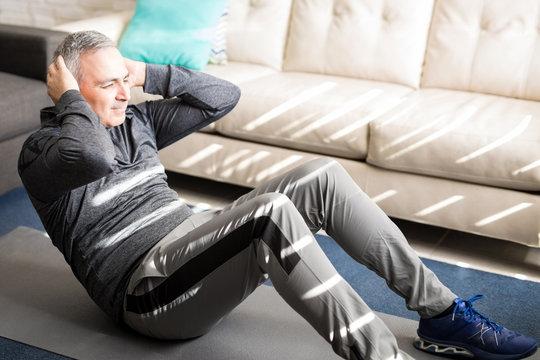 Healthy mature man exercising at home