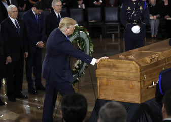 Trumps touches casket during ceremonies for the late Rev. Billy Graham in Washington