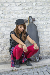 Young urban girl kneel in front of brick wall with skateboard beside her