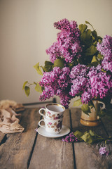 Close-up of cups with saucer by flower vase on wooden table