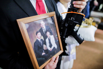 A man holds a portrait of his family next to his AR-15-style rifle as people attend a blessing ceremony with their AR-15-style rifles in their cases at the Sanctuary Church in Newfoundland