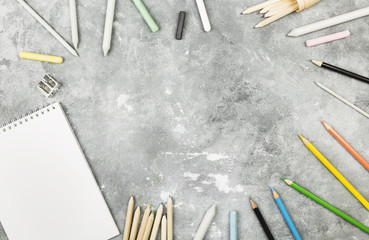 Accessories to drawing - colored pencils, pastel, white paper on a gray background. Top view, copy space