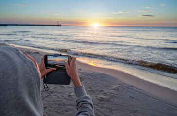 Young girl taking photo - beautiful summer sunset over Baltic sea.