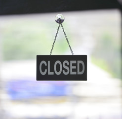 """Close"" sign board at a glass door in coffee shop"