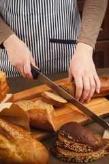 Woman cutting bread on wooden board