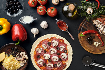 Raw pizza ingredients on black texture table background