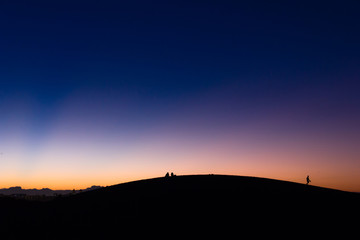 People silhouettes on top of Maspalomas sand dunes over fantastic sunset sky in Canary Islands, Spain. Minimal concept, aliens on another planet