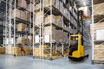Huge distribution warehouse with high shelves and forklift with operator.