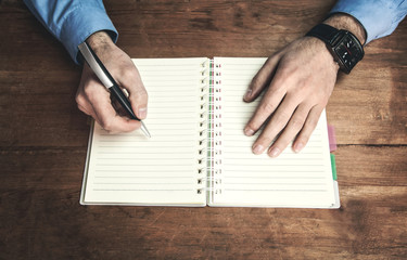 Man writing on notepad in the wooden desk.