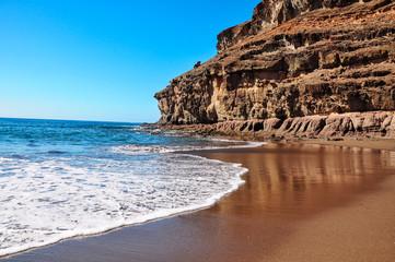 Calm water and blue sky in rustical beach Tiritaña. Bay framed by high cliffs in barranco near Taurito/Mogan. Between Punta de la Cruz de Piedra and Punta de los Medios Almudes. Gran Canaria