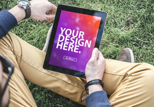 Tablet User Sitting on Grass Mockup 3