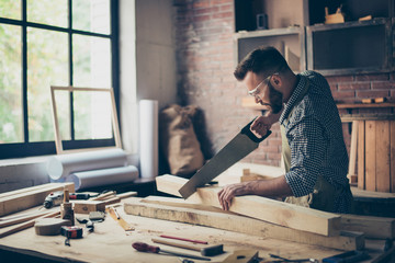 Concentrated strong confident professional handsome bearded wearing checkered shirt apron protective glasses is sawing a wooden plank with a handsaw in his workshop