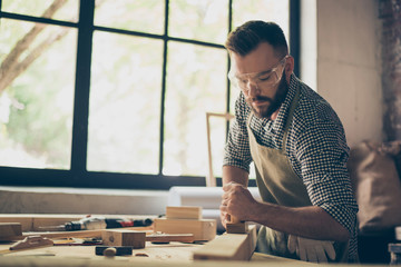 Confident professional busy hardworking bearded handsome serious wearing checkered casual shirt apron and protective goggles is aligning the surface of wooden plank with a plane near window