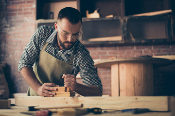 Confident successful concentrated gifted bearded woodworker clothed in checkered shirt apron and safety goggles is working with a plane is his workshop