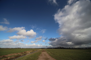 Big white clouds racing over the Zuidplaspolder in the Netherlands in blue sky