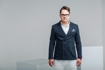 Modern businessman in blue suit, white trousers and glasses in studio on gray background.