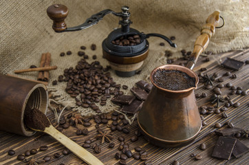 Devices and ingredients for making coffee.The wooden background is brown, burlap.