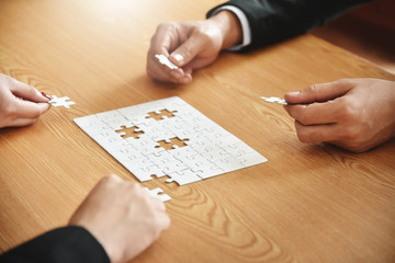 Business people hands are holding jigsaw puzzle.