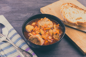 Braised pork with vegetables in a black bowl and a piece of bread on a rustic table