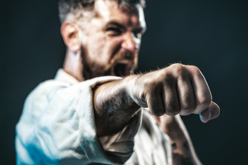 Strong, angry, bearded man dressed in kimono, shaking fist, portrait a screaming boxer. Selective focus on fist.